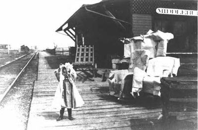 Photo of girl is standing in front of the Pumpkin Vine Railroad depot in Middlebury