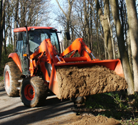 Photo of a tractor front loader delivering gravel to a trail repait site.