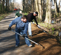 Photo of volunteers spreading gravel at a trail repair site.